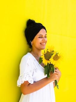 Ritratto verticale di una donna attraente e felice con i girasoli in posa contro un muro giallo