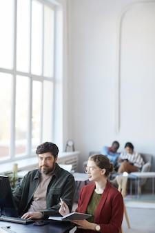 Ritratto verticale del manager barbuto che parla con una collega durante la riunione al tavolo all'interno dell'ufficio bianco, spazio copia