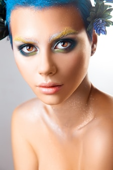 Ritratto verticale di bella ragazza con trucco multicolore e colpo dello studio dei capelli blu isolato