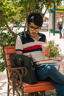 Ritratto verticale di un bel ragazzo affascinante con gli occhiali con un libro e una tazza di caffè in mano