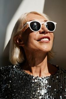 Ritratto verticale di bella donna matura che indossa un abito glamour illuminato dalla luce del sole contro il muro bianco