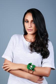 Ritratto verticale della ragazza araba castana sulla parete blu. ragazza mediorientale che indossa braccialetto verde moderno sulla parete blu