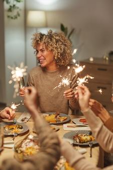 Ritratto verticale di spensierata donna di razza mista che tiene le stelle filanti mentre si gode la cena e la celebrazione con amici e familiari