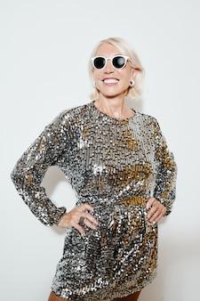 Ritratto verticale di una bella donna sorridente che indossa un abito glamour mentre posa alla festa contro il muro bianco, girato con il flash