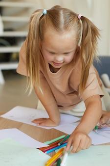 Ritratto verticale della ragazza bionda carina con sindrome di down che disegna e raggiunge le matite mentre ti godi la lezione di sviluppo