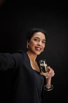 Ritratto verticale di elegante donna mediorientale tenendo il bicchiere di champagne e prendendo selfie foto mentre in piedi su sfondo nero alla festa, copia dello spazio