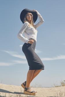 Ritratto verticale dal basso di una giovane donna vestita in camicetta bianca e gonna nera al ginocchio che indossa cappello a tesa larga ed enigmaticamente distoglie lo sguardo