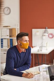 Ritratto verticale di bell'uomo maturo che indossa la maschera e la scrittura nel pianificatore mentre si lavora alla scrivania nel cubicolo dell'ufficio, copia dello spazio sopra