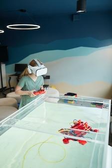 Ritratto verticale di un bambino che indossa un auricolare vr mentre utilizza una barca robotica nel laboratorio della scuola, copia spazio