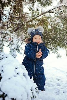 Ritratto verticale di un bambino che ride su una neve vicino a un abete