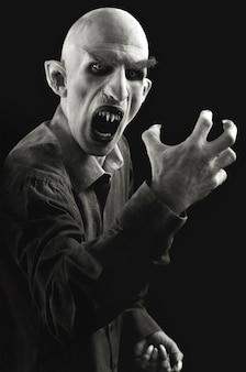 Ritratto verticale di un uomo contrassegnato come un vampiro su sfondo nero.
