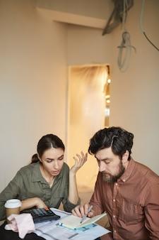 Ritratto verticale della coppia sposata budgeting ridecorazioni costano seduti a tavola nella stanza vuota, copia dello spazio