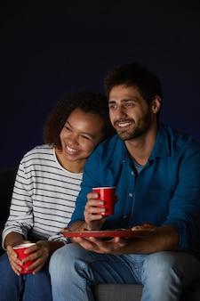 Ritratto verticale di giovani coppie di razza mista che guardano film a casa mentre mangiano snack e popcorn seduto sul divano in camera oscura