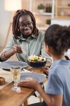 Ritratto verticale della moderna famiglia afro-americana che si gode la cena insieme a casa, concentrarsi sulla giovane donna sorridente che condivide il pasto fatto in casa con la figlia
