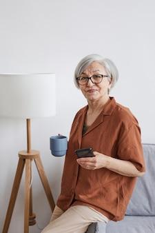 Ritratto verticale di una moderna donna d'affari senior che guarda la telecamera e si gode il caffè in interni minimi