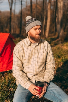 Ritratto verticale di un giovane hipster barbuto seduto fuori dalla sua tenda nel bosco.