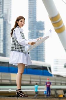 Ritratto verticale di una giovane donna asiatica adulta sorridente carina in abiti eleganti e casual in piedi, con in mano una mappa della città di carta e guardando la telecamera con uno sfondo sfocato di un edificio alto