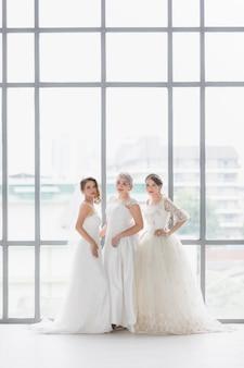 Ritratto verticale di un gruppo di belle spose asiatiche in piedi e pose.