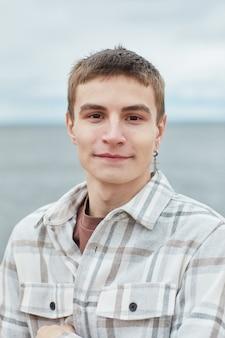 Ritratto verticale di un giovane sorridente che guarda l'obbiettivo sulla spiaggia con il cielo sullo sfondo