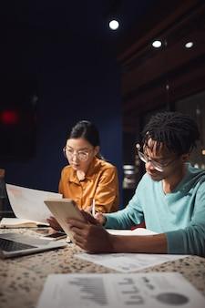 Ritratto verticale di due persone di affari che parlano del progetto mentre si lavora fino a tardi in ufficio buio