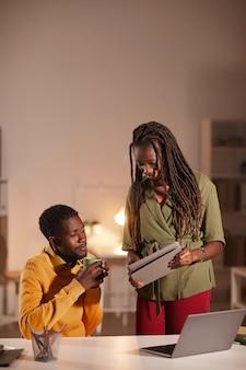 Ritratto verticale di due persone afro-americane contemporanee che parlano di progetto e guardando lo schermo del tablet mentre si lavora in ufficio