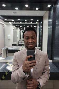 Ritratto verticale di giovane uomo d'affari afroamericano che prende selfie allo specchio in bagno pubblico