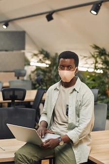 Ritratto verticale di giovane afro-americano che indossa la maschera e durante l'utilizzo di laptop in ufficio post pandemia