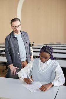 Ritratto verticale di una giovane donna afro-americana che fa l'esame al college con il professore che la guarda, copia spazio
