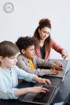 Ritratto verticale di una giovane insegnante che aiuta il ragazzo a usare il laptop durante la lezione di informatica a scuola