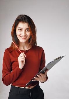 Ritratto verticale di una giovane donna in piedi con una matita in una mano e appunti in un'altra