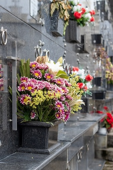 Messa a fuoco verticale poco profonda di mazzi di fiori sotto lapidi di marmo scuro al cimitero