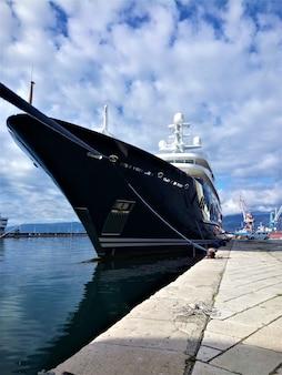 Ripresa verticale di una bellissima nave nera in un porto su un cielo nuvoloso