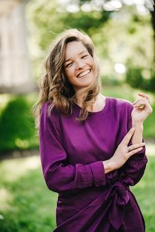 Colpo verticale di bella giovane donna con i capelli lunghi vestita in abito viola
