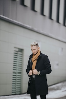 Colpo verticale di un uomo caucasico alla moda con una sciarpa marrone sul muro