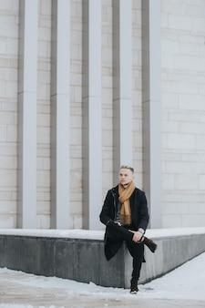 Colpo verticale di un uomo sexy alla moda caucasico con una sciarpa marrone seduto sul muro di cemento