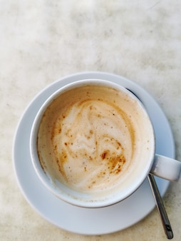 Ripresa verticale di una tazza di cappuccino con un cucchiaio su una superficie bianca