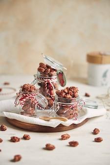 Colpo verticale di deliziose mandorle tostate di natale in un barattolo su un piatto di legno