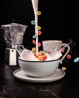 Colpo verticale di deliziosi anelli di frutta in una ciotola piena di latte con una tazza di caffè su un tavolo