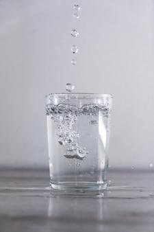 Colpo verticale di far cadere l'acqua in una tazza di vetro