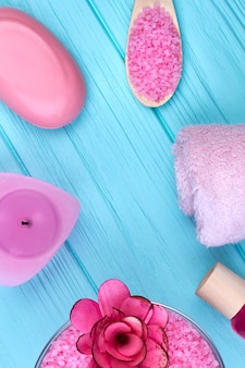 Accessori da bagno rosa piatti a posa verticale su legno blu