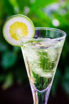 Colpo verticale di cocktail fresco con una fetta di lime