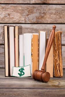 Libri del martelletto del colpo verticale e segno del dollaro. vecchio martello di legno del giudice. tangente del tribunale o segno di corruzione.