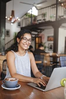 Colpo verticale dolce tenera donna urbana rilassata con gli occhiali che lavora da solo nella caffetteria