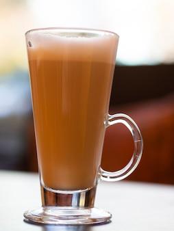 Colpo verticale di latte tazza di vetro con effetto bokeh