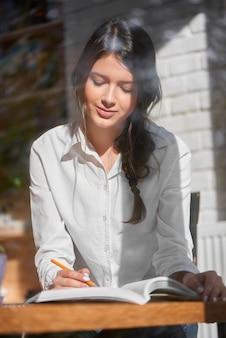 Colpo verticale di una splendida giovane donna dai capelli scuri che studia presso il caffè locale sul concetto di assegnazione di lavoro del progetto di lavoro di lettura intelligente degli studenti adolescenti del campus.