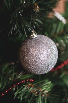 Colpo verticale di un giocattolo di natale grigio lucido su un capodanno decorato