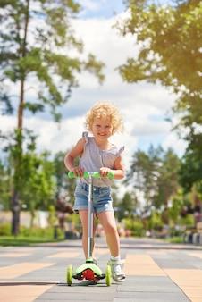 Colpo verticale di una piccola neonata felice che sorride mentre guida il motorino al parco.
