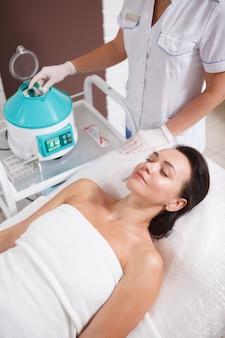Ripresa verticale di una donna matura che riceve un trattamento viso prp da un dermatologo