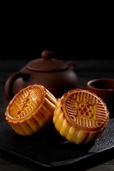 Colpo verticale di mooncakes con una tazza di tè su una superficie nera