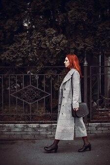 Ripresa verticale di una donna multirazziale che cammina vicino a un parco in città